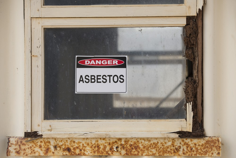 Asbestos danger warning sign on glass window at old rusty toxic contaminated building.